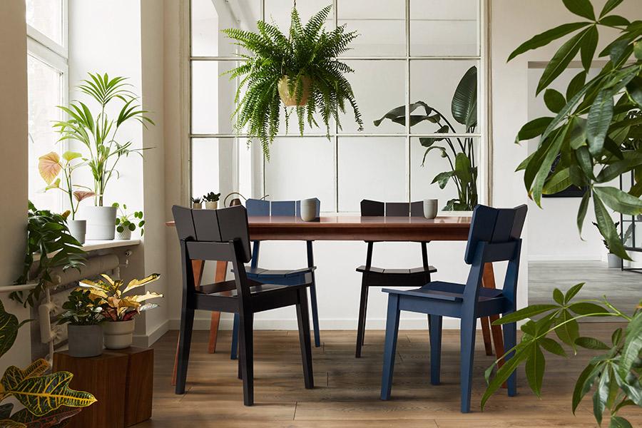 Sala de Jantar na varanda Urban Jungle, com uma Mesa de Madeira 6 Lugares e 4 cadeiras Uma coloridas.