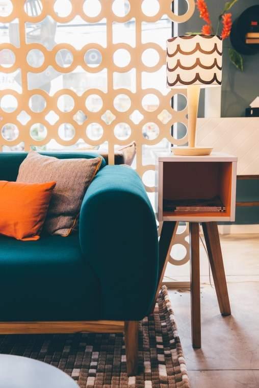Home office com sala e uma poltrona confortável combinando com o sofá.