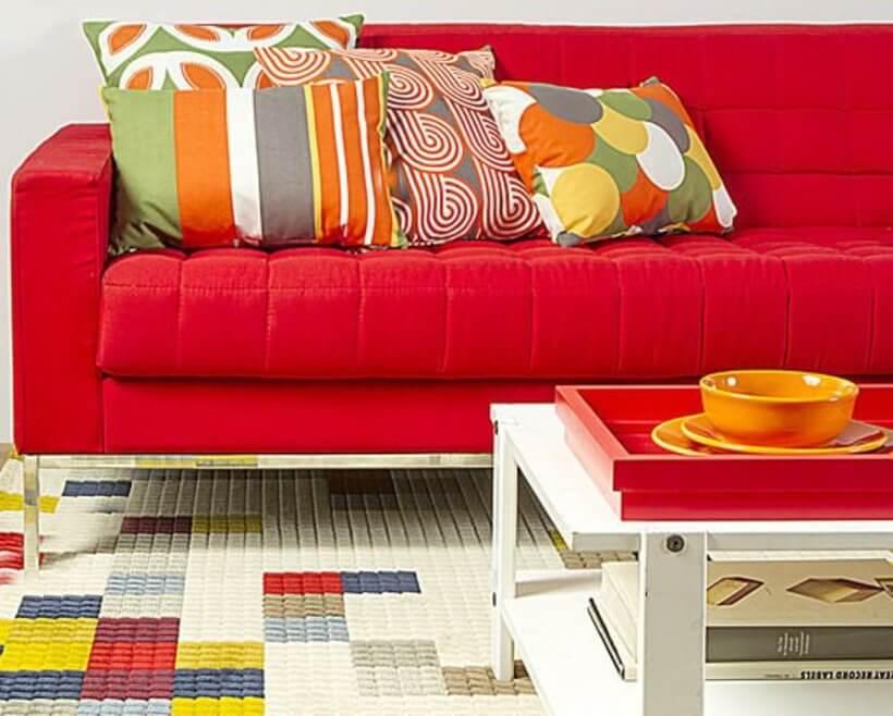 Outra sugestão para ajudar na escolha das almofadas é repetir as cores que aparecem no tapete da sala. (Almofada Pompeia Listras.) Foto: Oppa.