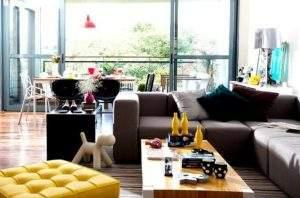 O sofá é a alma da decoração da sala. Aqui, o Sofá Modus Cinza recebe a companhia da Mesa de Centro Block e do Puff Barcelona Amarelo.