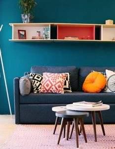 O sofá ganha vida com almofadas coloridas, como a linha de Almofadas Ozeki e a Almofada Zolly (amarela). O conjunto de Mesas Laterais Biscoito Fino acrescenta charme retrô à decoração.