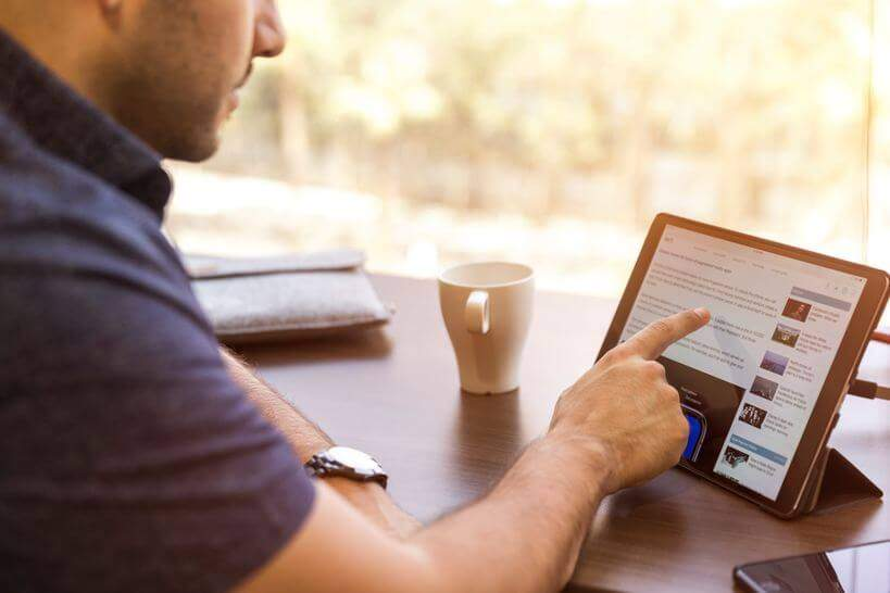 Homem procurando presentes de natal na internet no tablet