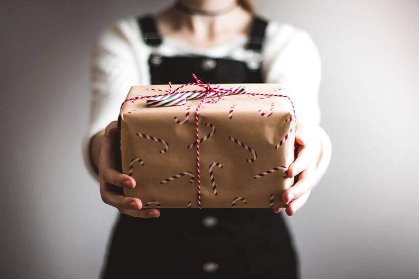 Mulher segurando pacote de presente embrulhado para natal