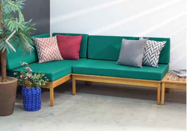 Sofá verde em varanda pequena com plantas.