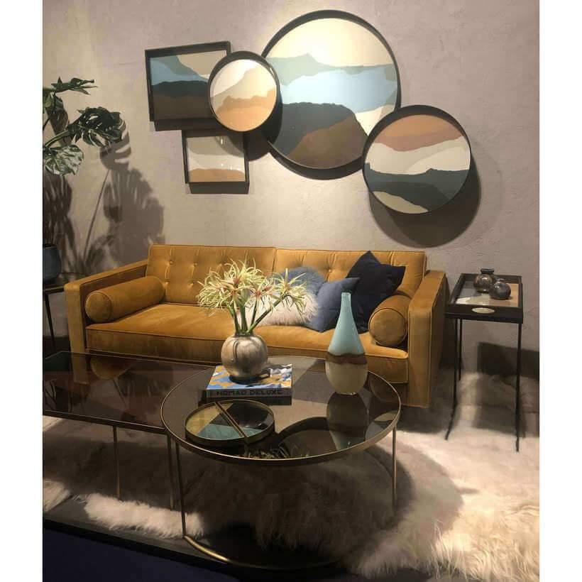 Tendência de decoração detectada: sobre o sofá amarelo-mostarda, um arranjo de bandejas na parede surpreende as visitas. Oppa! Tapetes e móveis de pelos seguem em alta. Foto: Viví Kolér.