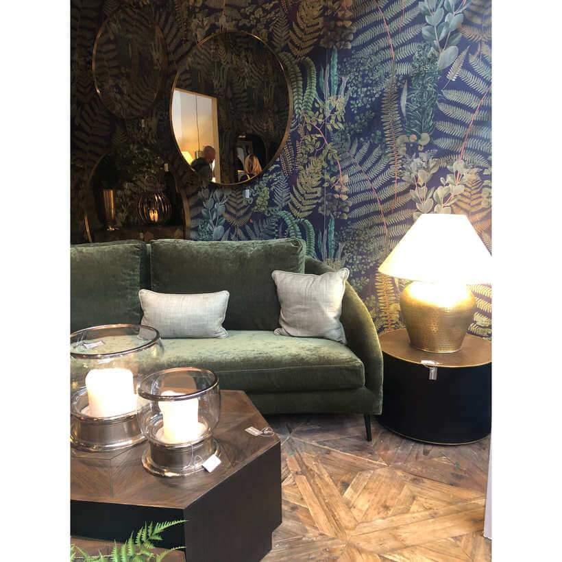 O sofá de veludo verde faz belo par com o papel de parede estampado. Foto: Viví Kolér.