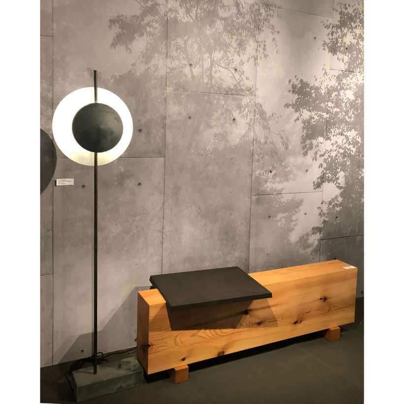 Cenário zen: diante do painel de concreto com a impressão de árvores, a luminária de piso escultórica ladeia o banco de madeira natural. Foto: Viví Kolér.