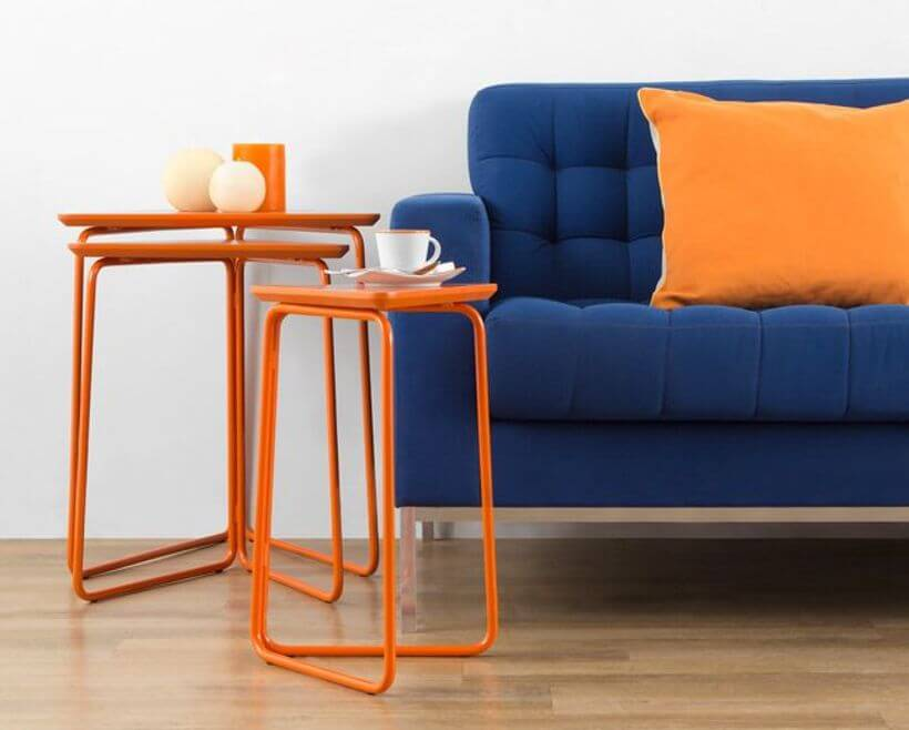 O laranja da almofada e do Conjunto de Mesa Lateral Trio (https://www.oppa.com.br/produto/conjunto-mesa-lateral-trio-laranja?p=Conjunto%20de%20Mesa%20Lateral%20Trio&ranking=3&typeclick=3&ac_pos=header) aquece a decoração da sala de estar (https://www.oppa.com.br/ambiente/sala-de-estar). Foto: Oppa.