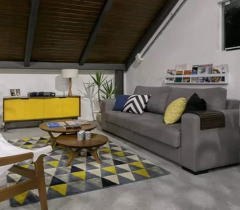 Note como a presença do amarelo traz vida à base cinza desta sala de estar. Foto: Oppa.