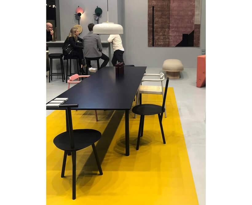 Por que não um tapete amarelo na sala de jantar (https://www.oppa.com.br/ambiente/sala-de-jantar) de móveis pretos? Foto: Viví Kolér / IMM Colônia.