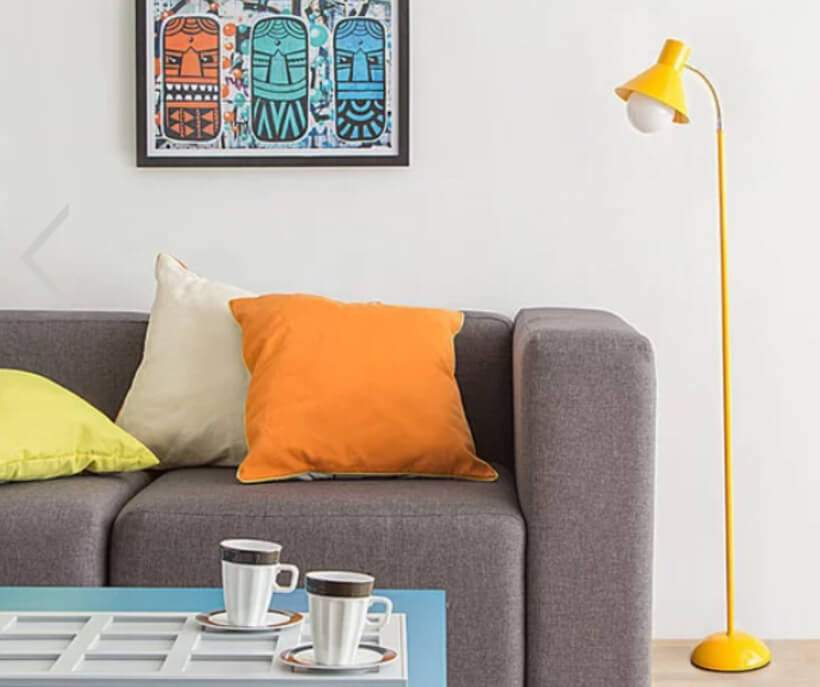 A Luminária de Piso Funchal (https://www.oppa.com.br/produto/luminaria-de-piso-funchal-amarela) ladeia o sofá cinza, enfeitado com almofadas (https://www.oppa.com.br/decoracao/almofadas) em tons cítricos. Foto: Oppa.