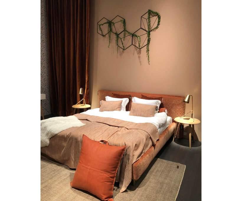Cama estofada de veludo laranja, com roupa de cama e almofadas em tom sobre tom. Foto: Viví Kolér / IMM Colônia.