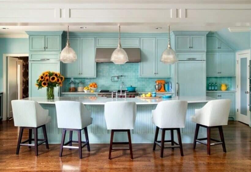 Bancada de cozinha com cadeiras.