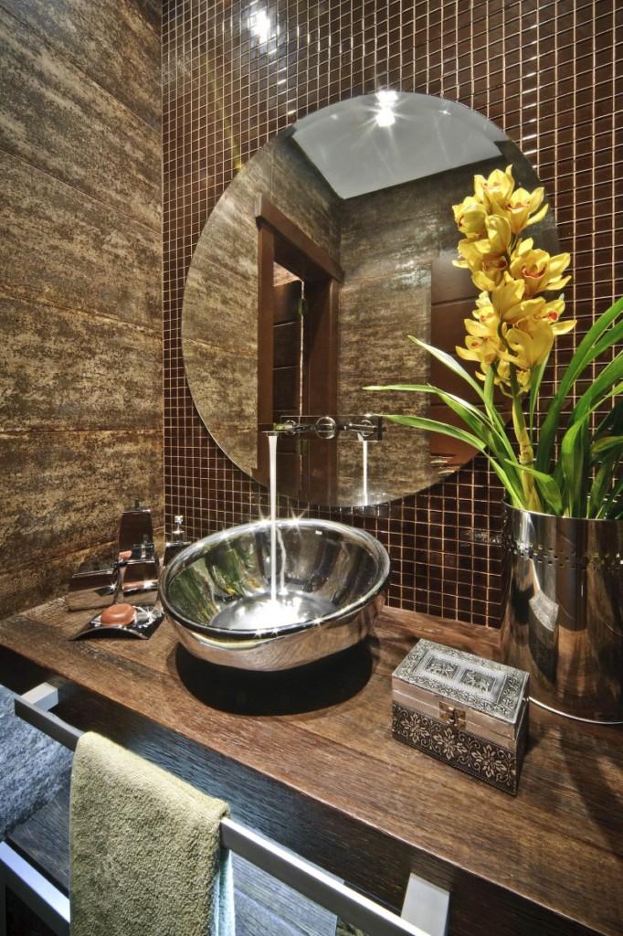 Banheiro escuro e sem muita luz natural com flores coloridas.